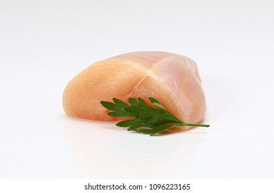 half of raw chicken breast garnished with parsley
