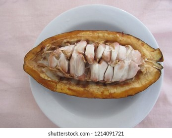 Half ripe cacao on white plate, viewed from above