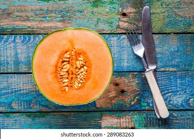 half ripe melon on a rustic wooden background with knife and fork
