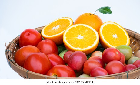 Half ripe orange Place a bamboo basket of fruits and vegetables high in vitamin C, such as ripe oranges, cucumbers and tomatoes on a white background.