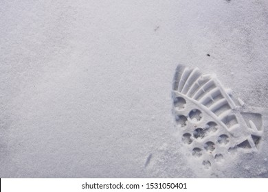 Half of the shoe print on the ground just after snow. Fresh snow has fine textures and details.