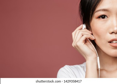 Half side portrait of brunette asian woman dressed in basic wear listening to music with earphones isolated over red background in studio