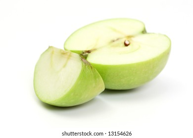 Half and slice green apple on white background