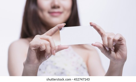 Half smiling face of young woman showing the white card with message No, selective focus on the card.