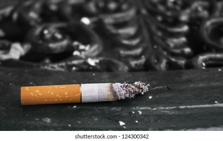 Half smoked cigarette (unbranded) on a park table with muted colors