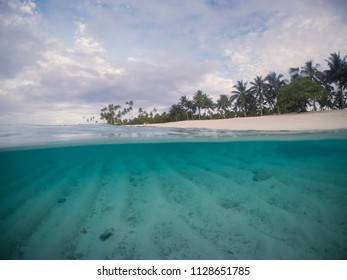 Half and half split scross section of clear sea and empty beach with palm trees at Matautu, Lefaga, Upolu Island, Western Samoa, South Pacific