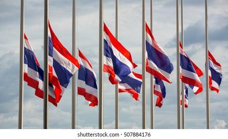 Half staff Thai flags against cloudy sky.