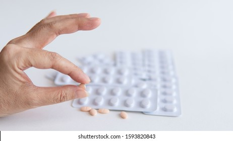 Half of statins tablets pill in female patient hand and white blister pack of them for light resistance packaging on white background, medicine for treatment hyperlipidemia
