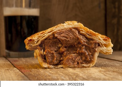 Half of a steak and ale pie on a wooden background