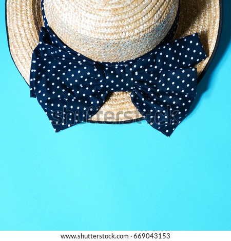 2abef4f1 Half of straw hat with big polka dot navy ribbon bow on green pastel  background,