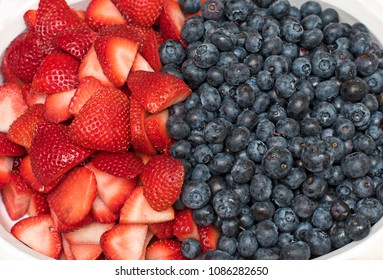 Half Strawberries and half Blueberries together. Strawberries cut into halves.
