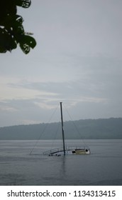A half submerged yacht is in a bay. The sky is overcast and the water is grey. The heads of some children can be seeh as they swim near the boat. A forest covered hill is in the background.