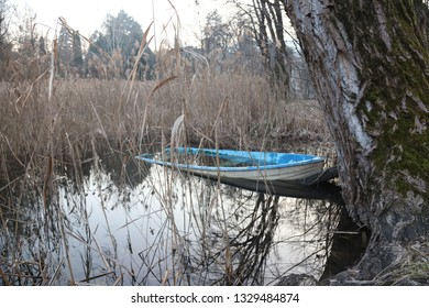 Half sunk abandoned boat try to float on a calm lake in the forest