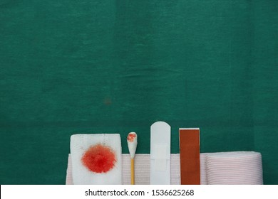 half tools includes plaster,swab,blood gauze and roll gauze on green surgical dress for clean wound with copy space