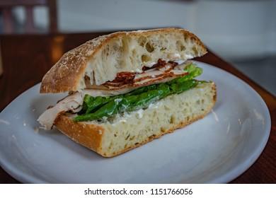 Half of a turkey sandwich on a french brioche bun.