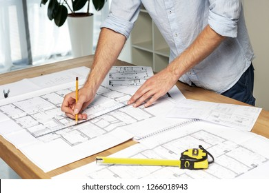 Half turn close up cropped concentrated focused confident success man in formal wear shirt stand at the table in light loft interior create interior at new house