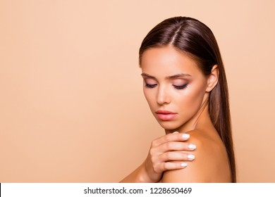 Half turn close up portrait of careless carefree brunette hair lady touch her naked shoulders she look down isolated on pastel beige background with copy space for text