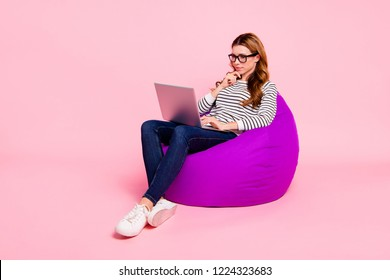 Half turn full legs body size lady with her trendy brown wave curly hair she isolated pink background sit in spectacles shoes striped casual clothes jeans denim wear look at pc gadget use internet
