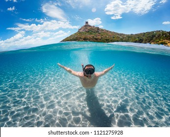 Half underwater photography with man diving under in turquoise sea with open arms as if he were flying under water - Sardinia, Villasimius Porto Giunco beach