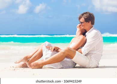 half view of happy young couple in white on the beach