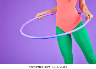 half view of unrecognizable fitness woman standing and holding hula hoop, doing aerobics exercises, has beautiful body curves, wearing pink leotard and green leggins, posing over purple background