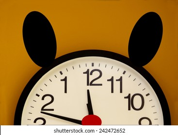 Half of a wall clock with red nose, black ears and the order of the numbers inverted