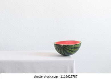 Half of watermelon on a white table with copy space. Creative still life