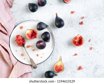Half and whole figs on gray cement or stone background. Figs flesh in teaspoon on plate and figs on tabletop. Top view or flat lay. Horizontal