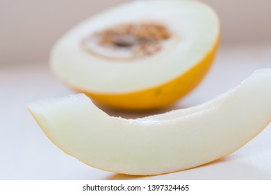 Half of yellow honeydew melon with seeds isolated on white background. Soft light.