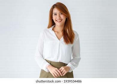 Half-body portrait shot of beautiful attractive smiling young adult Asian woman in formal long sleeve white shirt looking at the camera in studio isolated with white background