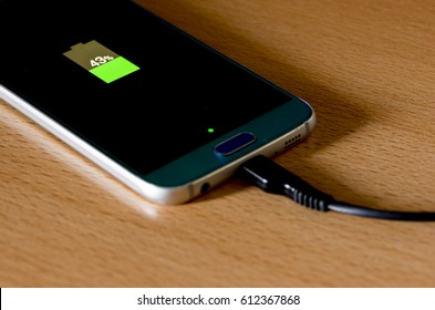 A half-charged mobile phone on top of the table