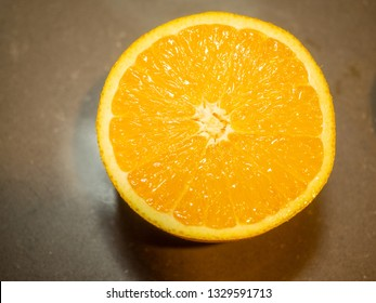 Half-cut orange without seeds, closeup of citrus on the board
