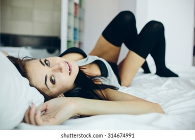 half-dressed beautiful young girl lies on a white bed