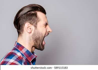 A half-face portrait of a young bearded yelling man with fashionable haircut isolated against gray background.