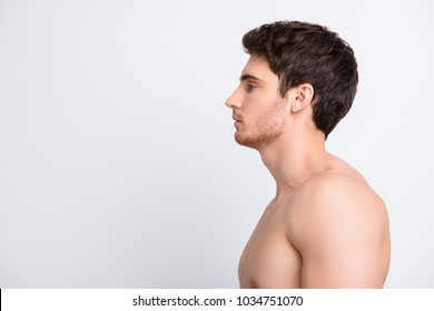 Half-faced profile side view portrait of confident sexy sporty modern guy with   perfect smooth soft skin, isolated on gray background, looking at copy space