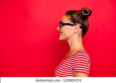 Half-faced side profile view portrait of happy confident woman dressed in striped shirt and spectacles isolated on red background with copy space for text