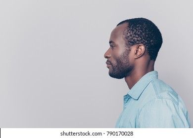 Half-faced side profile view portrait of thoughtful pensive serious confident handsome guy dressed in light blue shirt, isolated on grey background