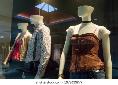 Half-headed mannequins in a store window that reflects surroundings