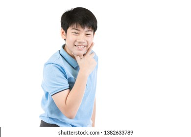 Half-length emotional portrait of asian young boy. Funny teenager pointing and looking upwards while smiling, isolated on white background. Handsome happy child pointing up