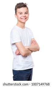Half-length emotional portrait of caucasian teen boy wearing white t-shirt. Funny teenager with arms folded, isolated on white background. Handsome child looking at camera.