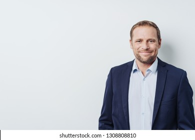 Half-length front portrait of handsome businessman without a necktie, standing against white background with copy space and smiling, while looking at camera