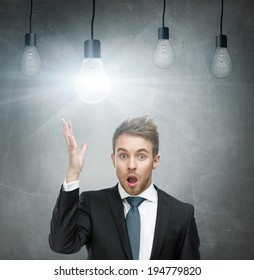 Half-length portrait of amazed businessman with open mouth and hand up and four light bulbs overhead. Concept of great idea and solution