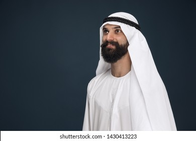 Half-length portrait of arabian saudi businessman on dark blue studio background. Young male model standing and smiling. Concept of business, finance, facial expression, human emotions.
