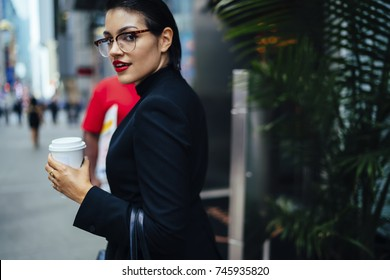 Half-length portrait of attractive confident business woman in elegant wear strolling on street in downtown, serious female executive manager in stylish eyeglasses and red lips looking at camera
