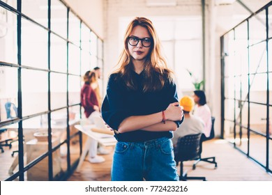 Half-length portrait of attractive female leader of working crew spending time in coworking office,confident woman in eyewear looking at camera posing with crossed arms on team working on background