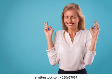 Half-length portrait of beautiful dreamy blonde wearing white classic blouse and black skirt standing crossing her fingers with closed eyes wanted to make her wishes come true. Isolated on blue