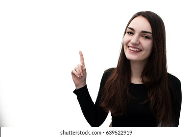 Half-length portrait of beautiful smiling woman with long hair and brown eyes in black blouse pointing up with blank text space