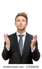 Half-length portrait of business man praying with hands up, isolated on white. Concept of hope and belief