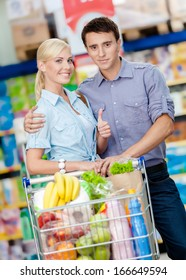 Half-length portrait of couple in the market with cart full of food. Concept of consumerism and healthy food