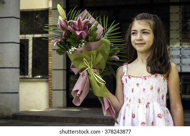 Half-length portrait eight-year girl with the bouquet in the hands